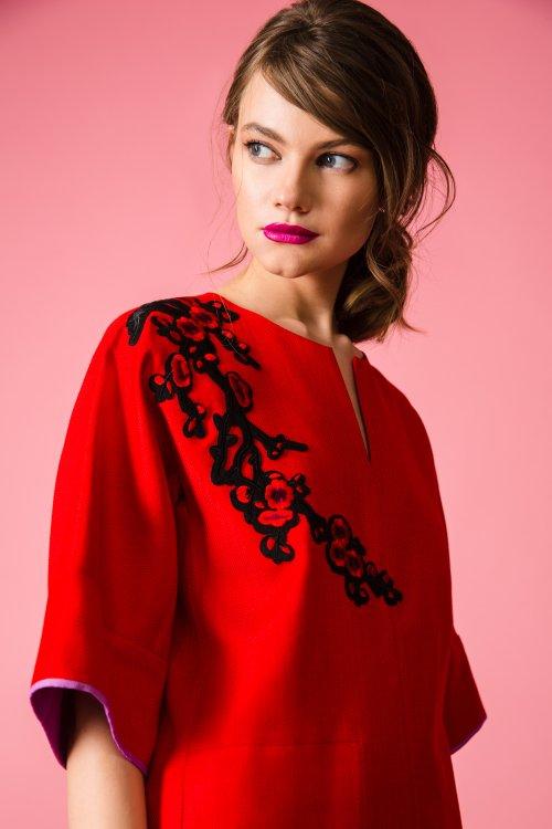Прямое красное платье с фигурным вырезом и декоративной аппликацией на правом плече.