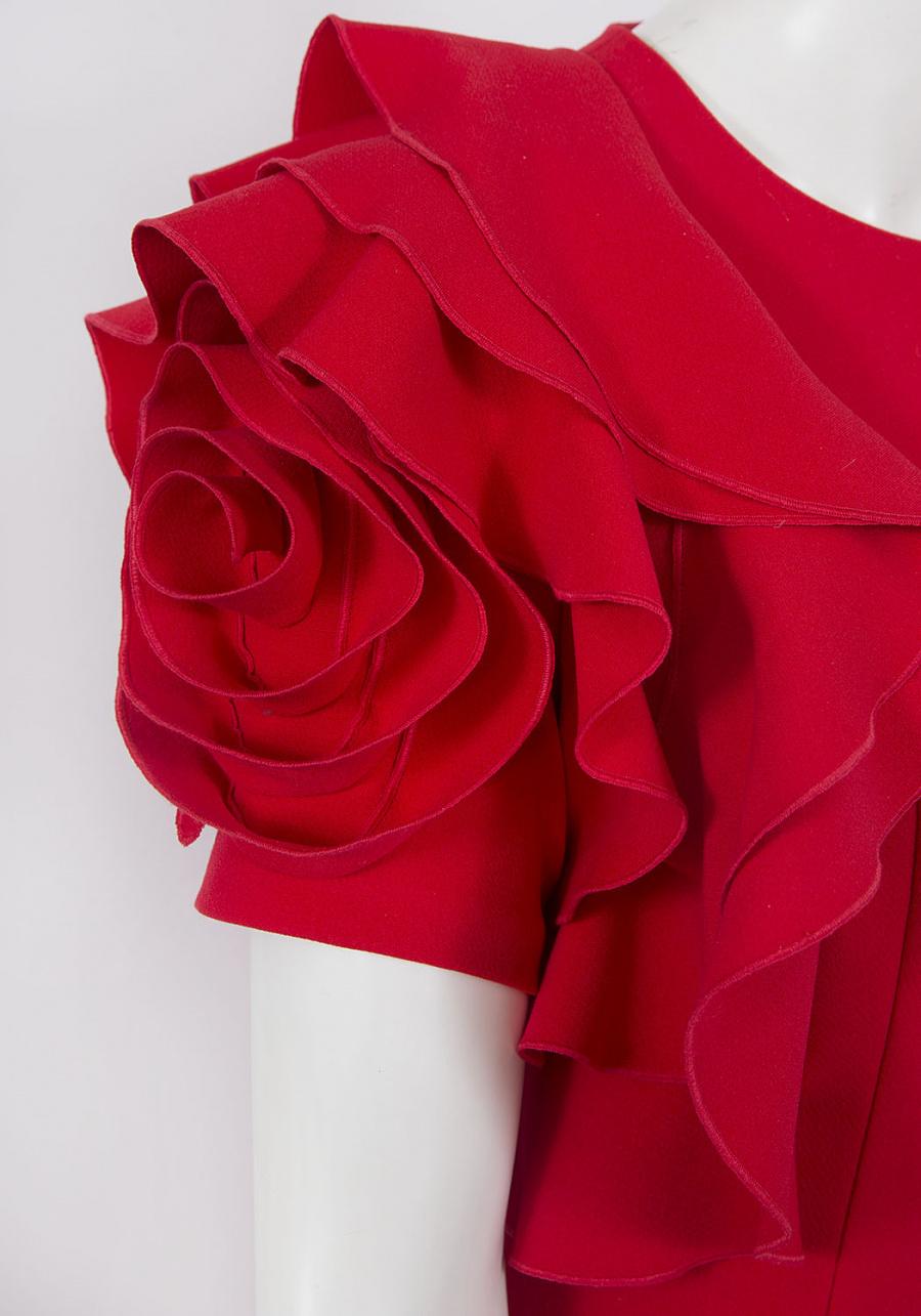 Красное платье полуприлегающего силуэта с декоративным цветком в области плеча.
