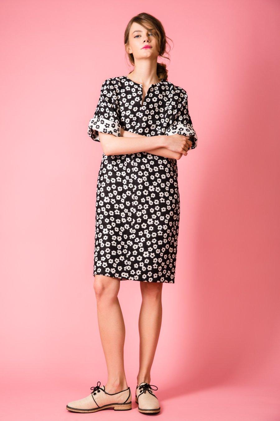 Прямое черное платье в белый цветочек с фигурным вырезом и цельновыкроенными рукавами.
